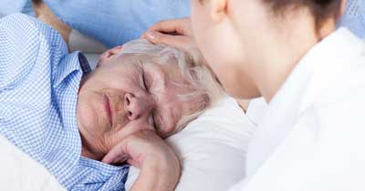 Elderly woman looking over her shoulder at private caregiver