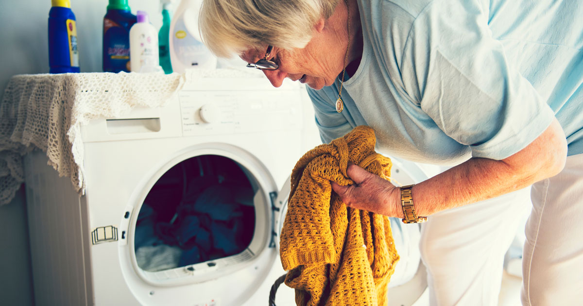 Elderly woman doing her laundry - needs help at home.