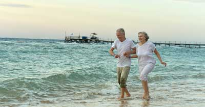 Elderly couple walking along the beach on vacation