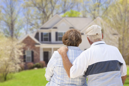 Elderly couple outside admiring their home