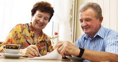 Elderly couple reviewing long term care policy papers
