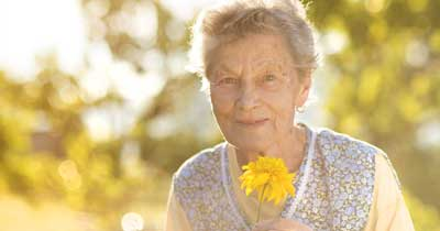 Elderly Woman with Alzheimers Holding Flower